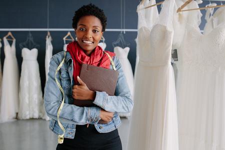 Portret właściciela sklepu z sukniami ślubnymi z pamiętnikiem. Krawcowa kobieta w swoim butiku ślubnym.