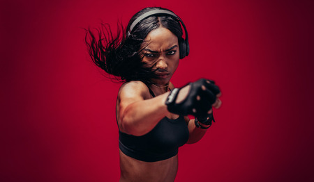 Boxer practicing her punches in a studio. African female boxer practicing boxing against red background. Archivio Fotografico