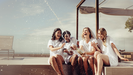 Cheerful bride and bridesmaids celebrating hen party with champagne while sitting on rooftop. Girls having a great time at the hen party. Banco de Imagens