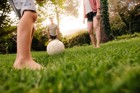 Football on grass with family standing around outdoors in park. Legs of little boy about to play football with his parents in garden.