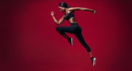 Femme sportive qui court sur fond rouge. Photo de pleine longueur de femme africaine en bonne santé, sprint.