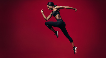 Sports woman running over red background. Full length shot of healthy young african woman sprinting. 版權商用圖片 - 93156167