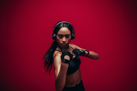African woman practising boxing in studio. Fit young female boxer with headphones exercising on red background