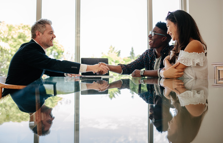 Male real estate broker shaking hands with new property owners while sitting across a table. Property seller congratulating couple on making deal on new house.