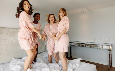 Bride and bridesmaids jumping on bed before wedding. Females having a great time at the hen-party, jumping on bed and smiling. Stock Photo
