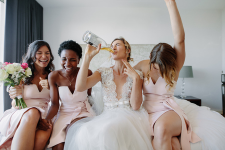 Bride in white dress drinking a bottle of wine while sitting on bed with bridesmaids. Bride and bridesmaids enjoying before wedding in hotel room.