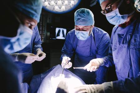 Doctors during surgery in hospital. Team of professional surgeons working at the hospital performing surgical procedure in operating theatre. Stock Photo