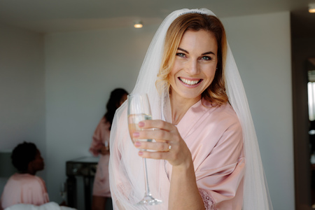 Happy young woman drinking champagne at bachelorette party in bedroom. Pretty young bride celebrating hen party with friends at home.