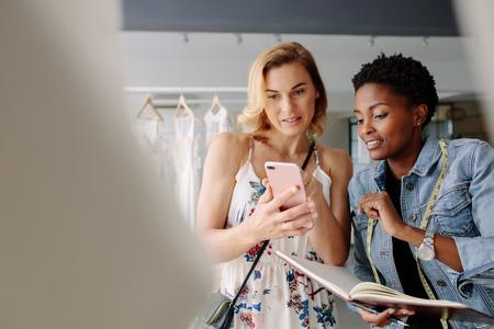 신부 입고 드레스 패턴에 그녀의 휴대 전화에 신부 착용 패턴을 보여주는 여자. 쇼핑 조교와 신부 부티크에서 결혼식 복장에 대 한 쇼핑 신부.