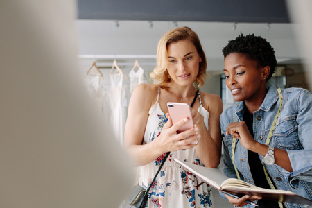 Woman showing a bridal wear pattern on her mobile phone to bridal dress tailor. Bride shopping for wedding outfit in bridal boutique with shop assistant.