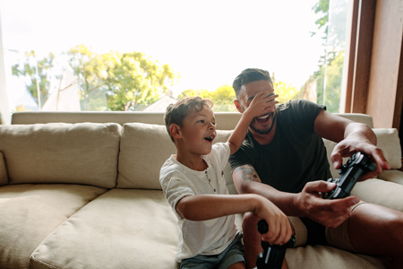 Little boy covering eyes of his father playing video game. Cheerful family of father and son having fun playing video games at home. Reklamní fotografie