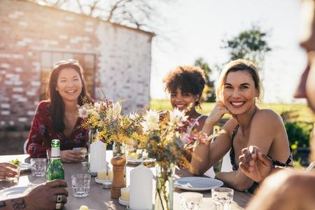 Jongeren feesten in een restaurant buitenshuis. Multiraciale vrienden zitten samen rond een tafel en glimlachen tijdens tuinfeest. Stockfoto