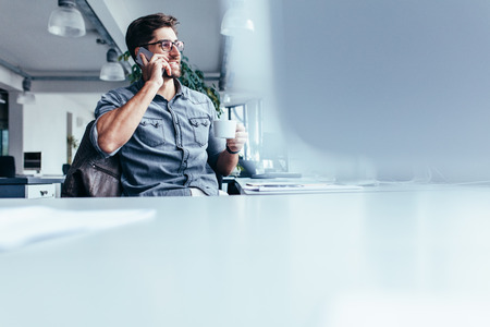 Young man with cup of coffee and talking on mobile phone. Male designer sitting in office having coffee and making phone call.