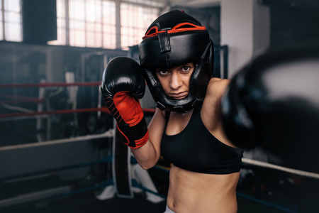 Female boxer throwing punches inside a boxing ring. Woman in boxing head gear and gloves boxing inside a ring.