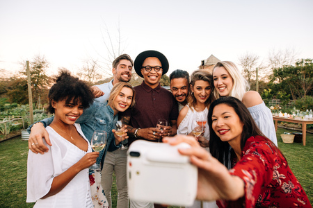 Woman with friends taking selfie using instant camera. Group selfie at outdoor party.