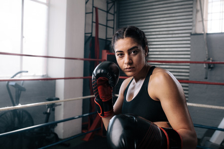 Close up of a female boxer doing shadow boxing inside a boxing ring. Boxer practicing her punches at a boxing studio. Reklamní fotografie
