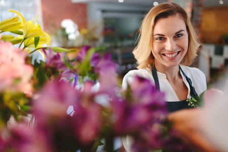 Young successful small business owner florist in her own flower shop smiling happily. Caucasian woman smiling at florist shop.