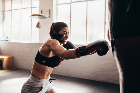 Female boxer hitting a huge punching bag at a boxing studio. Woman boxer training hard. Фото со стока