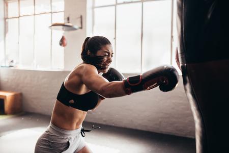 Weiblicher Boxer, der einen sehr großen Sandsack an einem Verpackenstudio schlägt. Frauenboxer, der stark ausbildet. Standard-Bild