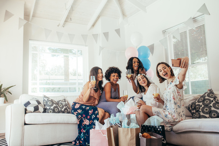 Group of female friends making self portrait in baby shower party. Group of diverse women friends meeting for baby shower at home.