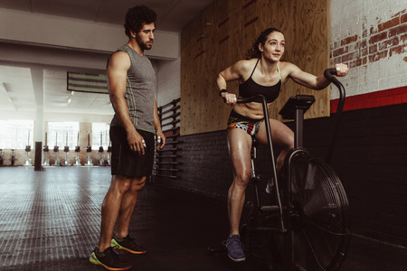 Fitness female using air bike for cardio workout at gym with personal trainer. Woman doing intense workout on gym bike with male coach.