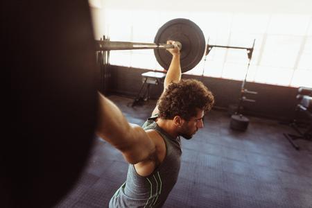 バーベルで運動する筋肉の男。クロストレーニングジムで重い体重で運動する若い男をフィット。 写真素材