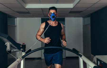 Portrait of runner wearing mask on treadmill in sports science laboratory. Sports man running on treadmill and monitoring his fitness performance. Stock Photo
