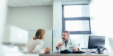 Male physician talking to a patient during consultation at his office. Mature doctor explaining diagnosis to female patient.