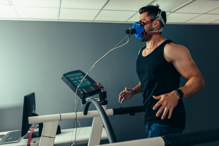 Fitness man running on treadmill with a mask testing his performance. Athlete examining his performance in sports science lab.