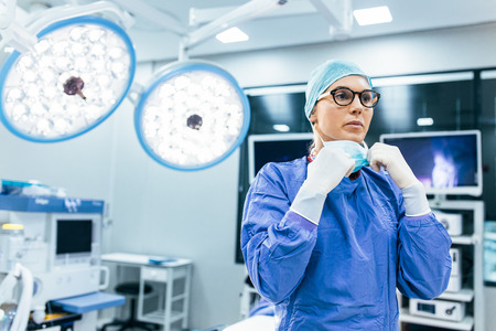 Female surgeon with surgical mask at operating room. Young woman doctor in surgical uniform in hospital operation theater. Stock Photo