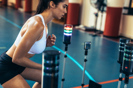Female athlete using a visual stimulus system. Sportswoman at sports lab exercising with lights around. Reaction time training session at gym.