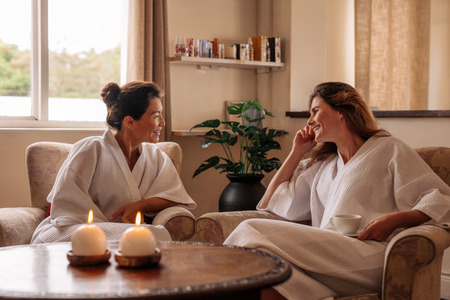 Two female friends chatting while waiting in spa reception area. Women in bathrobe sitting on chairs and talking at health spa.