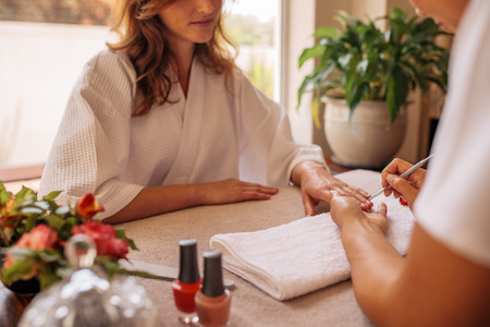 Top view of female hands in salon receiving a manicure by beautician. Manicurist shaping and polishing female clients nails at spa beauty salon.