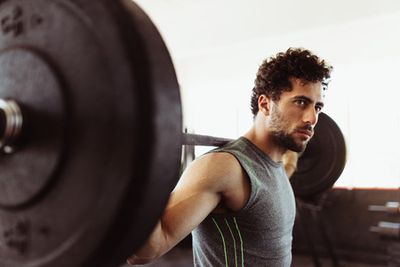 Healthy young guy at gym exercising with barbell. Fit young man working out with heavy weights at cross training gym. Stock Photo