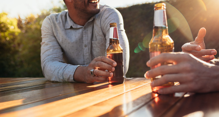Couple sitting outdoors at wooden table having beers and talking. Focus on couple hands with beer bottles during a outdoor party.