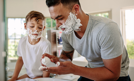 Father and son applying shaving foam on their faces in bathroom. Man and little boy putting shaving foam on their faces while shaving in bathroom.