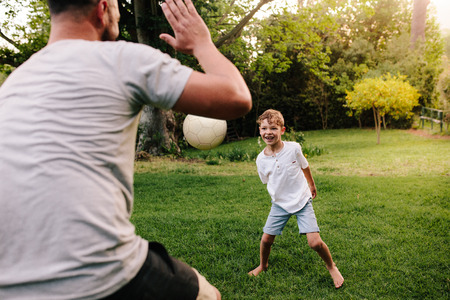 Happy little boy playing passing the ball game with his father. Happy young family playing with ball and having fun in backyard lawn. Stock Photo - 93607207