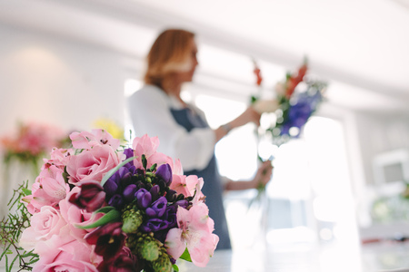 Colorful flower bouquet on counter with female florist working in background. Focus on fresh flower bouquet at florist shop.