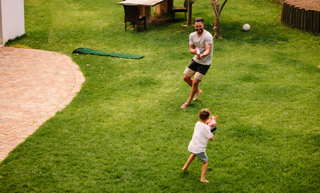 Father and son playing with water guns outdoors. Man and little boy spraying water from a gun in backyard lawn.