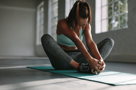 Young woman working out in gym. Female doing yoga exercise in butterfly pose.