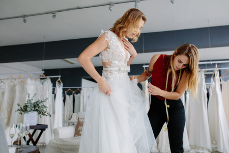 Female Making Adjustment To Wedding Gown In Fashion Designer.. Stock ...