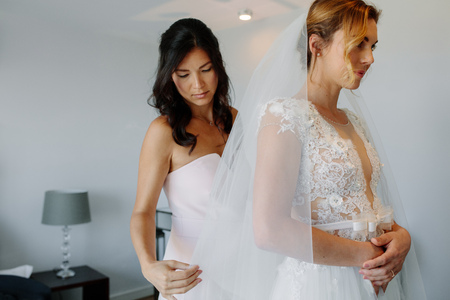 Bridesmaid helping bride to put on a veil. Beautiful bride and bridesmaids during the wedding preparations.