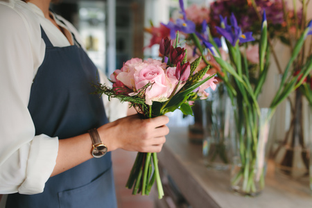 Close up of female florist hands holding flowers. Woman arranging various flowers for making a bouquet.