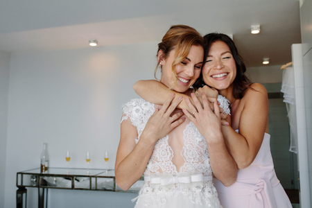 Happy bridesmaid giving a tender hug to bride in hotel room. Asian woman embracing her friend on her wedding day.