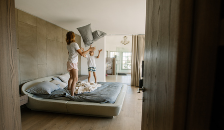 Mother and son standing on bed and playing with pillows. Young woman and little boy playing with pillows in bedroom.
