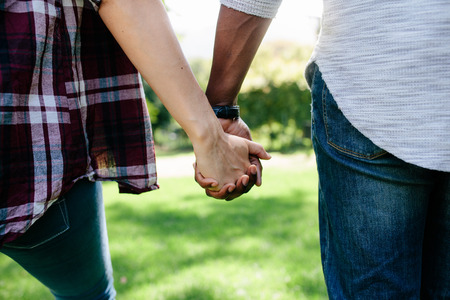 Close up of couple holding hands and walking outdoors. Rear view of man and woman holding hands of each other while walking in a park. Archivio Fotografico