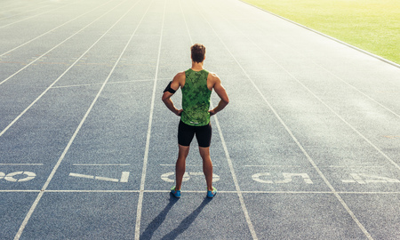 Rear view of an athlete standing on an all-weather running track. Runner standing at the start line with hands on waist. 写真素材