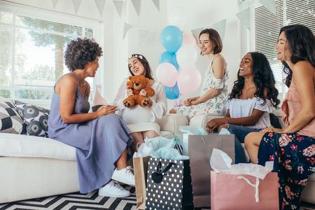 Schwangere Frau, die Babypartyparty mit Freunden feiert. Schwangere Frau, die Geschenke von den Freunden empfängt.