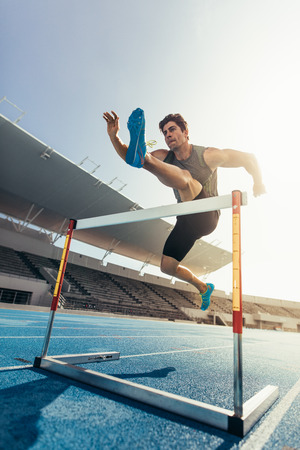 Runner jumping over an hurdle during track and field event. Athlete running a hurdle race in a stadium. Stock Photo