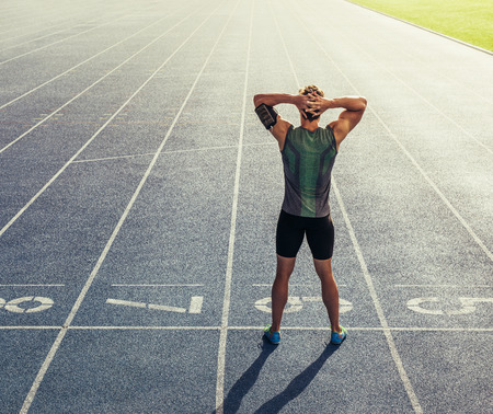 Hintere Ansicht eines Athleten , der auf einen Laufbahn mit den Händen am Kopf steht . Läufer bereitet sich auf die Pause in der Startlinie auf der Rennstrecke vorbereiten Standard-Bild - 93711088